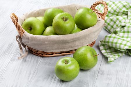 wooden basket: Green apples in basket over wooden table