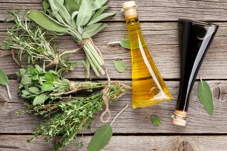 condiment: Fresh garden herbs and condiments on wooden table. Top view Stock Photo