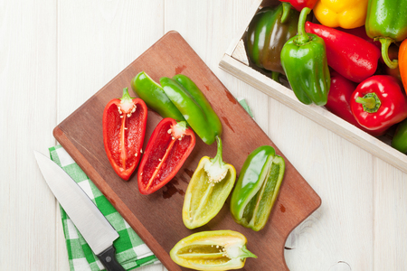green pepper: Fresh colorful bell peppers cooking on wooden table Stock Photo