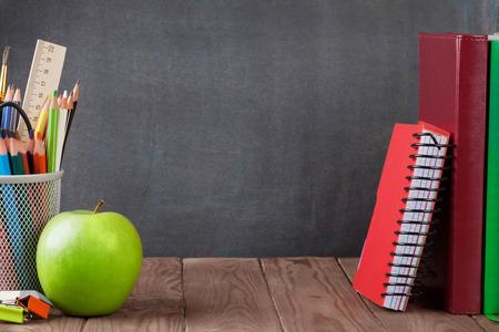 útiles escolares y de oficina y la manzana en la tabla de aula en frente de la pizarra. Ver con espacio de copia