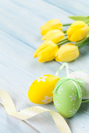 white tulip: Easter eggs and yellow tulips over wooden background with copy space