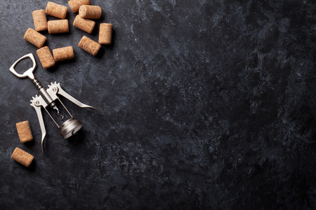 Wine corks and corkscrew over dark stone background. Top view with copy space Stock Photo