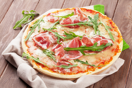 Pizza with prosciutto and mozzarella on wooden table