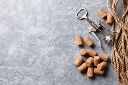 tornillo: Wine corks and corkscrew over stone background. Top view with copy space Foto de archivo
