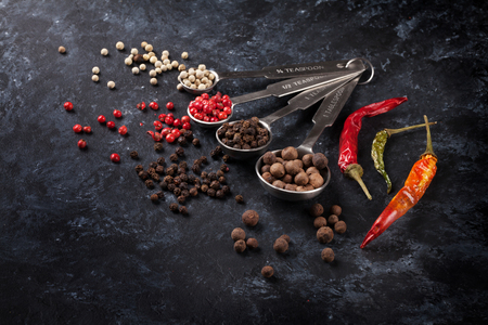 spicy cooking: Various peppercorn and chili pepper on black stone table