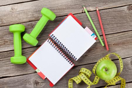 alimentos saludables: Mancuernas, manzana, cinta métrica y el bloc de notas para copiar el espacio Foto de archivo
