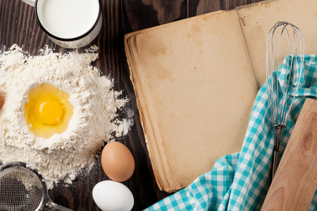 recipe background: Blank vintage recipe cooking book, utensils and ingredients on wooden table. Top view with copy space