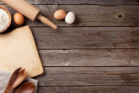 Keukentafel met lege vintage recept kookboek, keukengerei en ingrediënten. Bovenaanzicht met een kopie ruimte Stockfoto