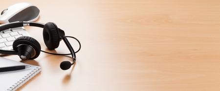 Schreibtisch mit Headset auf der Tastatur.