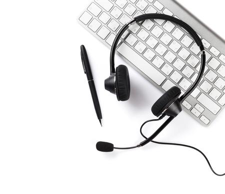 klawiatura: Słuchawki, pióro i klawiatura. Centrum telefoniczne wsparcie. Pojedynczo na białym tle Zdjęcie Seryjne