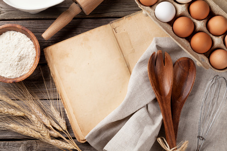 cooking utensil: Blank vintage recipe cooking book, utensils and ingredients on wooden table. Top view with copy space