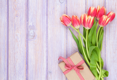 flores moradas: Colorful tulips and gift box on wooden table. Top view with copy space