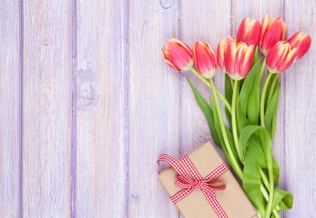 and bouquet: Tulipani colorati e confezioni regalo su tavola di legno. Vista dall'alto con spazio di copia