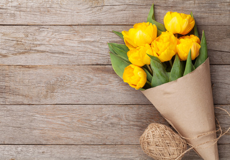 Yellow tulips over wooden table background with copy space