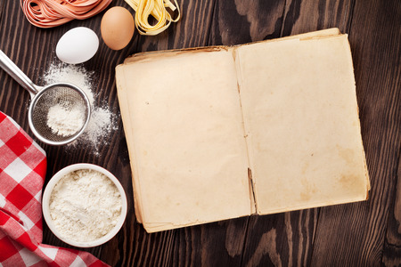 kitchen table top: Homemade pasta cooking and vintage cooking book on wooden table. Top view with copy space Stock Photo