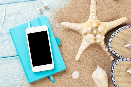 flip phone: Smartphone and notepad on wooden table with starfish and shells. Top view with copy space