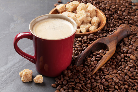 hot drink: Coffee cup, beans and brown sugar on stone table Stock Photo
