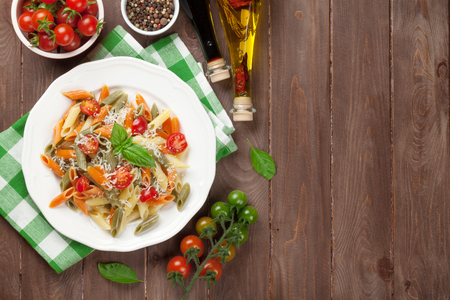 italian cuisine: Colorful penne pasta with tomatoes and basil on wooden table. Top view with copy space