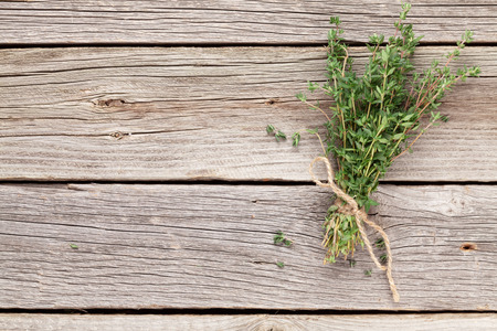 Bunch of garden thyme herb on wooden table. Top view with copy space