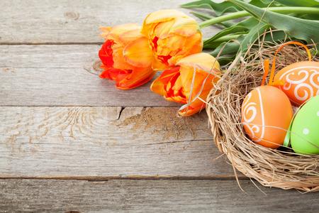 Huevos de Pascua en flores de nido y tulipán en la mesa de madera. Vista con espacio de copia