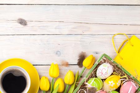 다채로운 계란 및 흰색 나무 위에 노란색 튤립 부활절 배경. 복사 공간이있는 상위 뷰