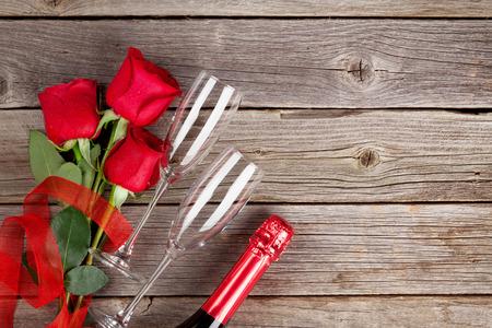 Rosas rojas y champán sobre fondo de madera. Vista superior con espacio de copia