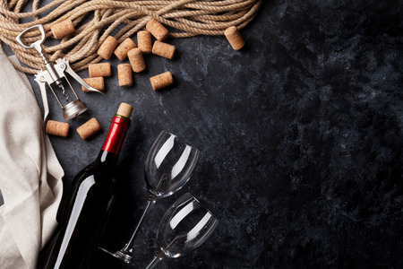 Wine, glasses and corkscrew over stone background. Top view with copy space