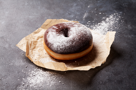donut: Chocolate donut on stone table Stock Photo