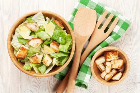 ensalada cesar: Fresh healthy caesar salad on wooden table. Top view Foto de archivo