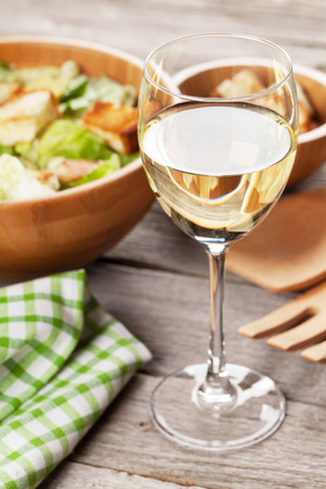 white wine: Fresh healthy caesar salad and white wine glass on wooden table