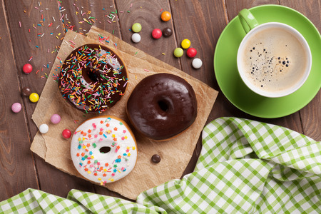 Donuts and coffee on wooden table. Top view