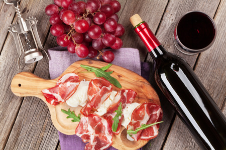 red wine bottle: Prosciutto and mozzarella with red wine on wooden table. Top view