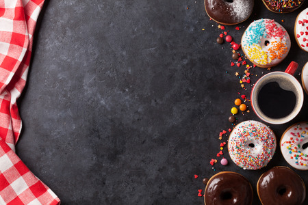 donuts: Donuts and coffee on stone table. Top view with copy space Stock Photo