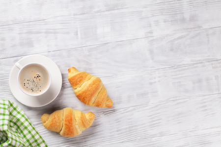 Fresh croissants and coffee on wooden table. Top view with copy space
