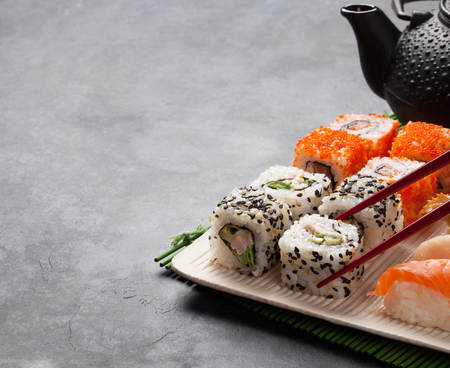 Set of sushi and maki roll and green tea on stone table. View with copy space Stock Photo