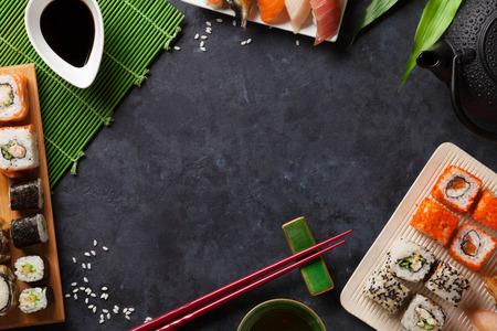 Set von Sushi und Maki-Rolle und grüner Tee über Steintisch. Ansicht von oben mit Kopie Raum