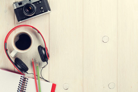 sound of music: Set of travel stuff. Camera, headphones, notepad and coffee cup on wooden table. Top view with copy space. Retro toned