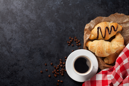 Fresh croissants and coffee on stone table. Top view with copy space