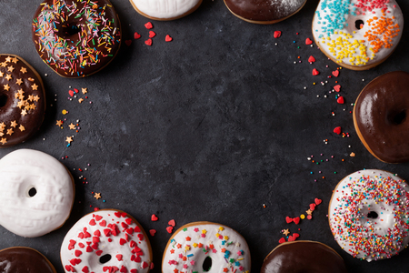 Colorful donuts on stone table. Top view with copy space Stock Photo