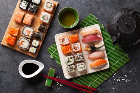 japones bambu: Conjunto de sushi y maki roll y el té verde en la mesa de piedra. Vista superior