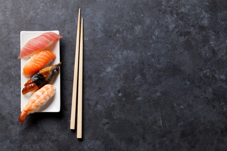 Sushi set and chopsticks on stone table. Top view with copy space Imagens
