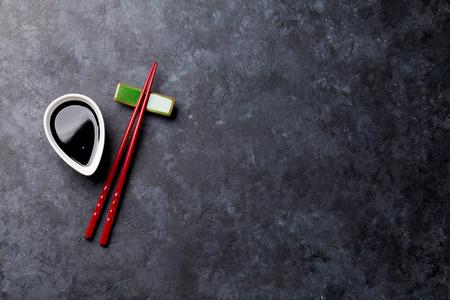 Sushi shopsticks en sojasaus op stenen tafel. Bovenaanzicht met een kopie ruimte
