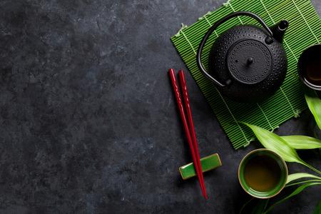 Grüner Tee und Sushi-Stäbchen auf Steintisch. Ansicht von oben mit Kopie Raum
