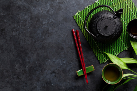 japanese background: Green tea and sushi chopsticks on stone table. Top view with copy space