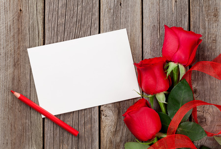 rose photo: Red roses and greeting card over wooden background. Top view with copy space Stock Photo