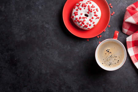 stone background: Donut and coffee on stone table. Top view with copy space