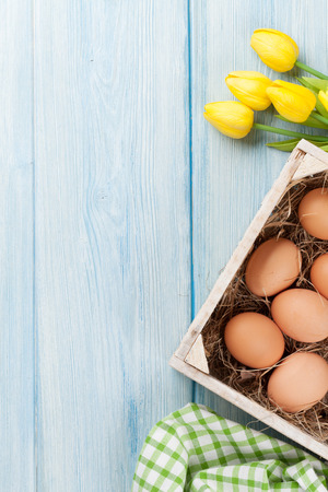 egg box: Easter eggs and yellow tulips over wooden background with copy space