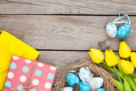 egg box: Easter background with blue and white eggs in nest, yellow tulips and gift box. Top view with copy space