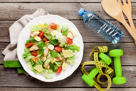 CHICKEN CAESAR SALAD: Fresh healthy diet salad on wooden table. Top view