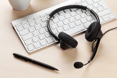 center table: Office desk with headset laying on keyboard. Call center table Stock Photo